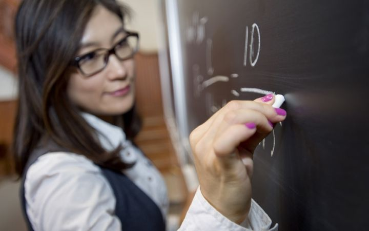 teacher writes on a blackboard